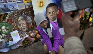 FILE - In this Saturday June 29, 2013 file photo, a child has their photograph taken by their parents next to paintings of President Barack Obama, center, and former South African President Nelson Mandela, left, outside the Mediclinic Heart Hospital where Nelson Mandela is being treated in Pretoria, South Africa. Africa was electrified by the rise of Barack Obama, the first U.S. president of African descent, who took aim at the twin scourges of corruption and dictatorship and sent thousands of troops to fight one of the most terrifying disease outbreaks in decades. (AP Photo/Ben Curtis, File)