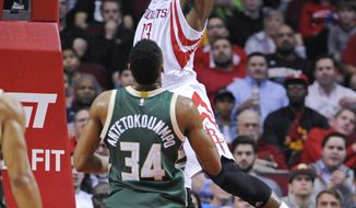 Houston Rockets guard James Harden (13) dunks as Milwaukee Bucks forward Giannis Antetokounmpo (34) looks on in the first half of an NBA basketball game, Wednesday, Jan. 18, 2017, in Houston. (AP Photo/Eric Christian Smith)