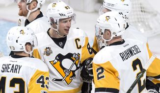 Pittsburgh Penguins' Sidney Crosby, center, celebrates a goal by Olli Maatta, hidden, with teammates Conor Sheary, left, and Chad Ruhwedel as they face the Montreal Canadiens during the third period of an NHL hockey game, Wednesday, Jan. 18, 2017 in Montreal. (Paul Chiasson/The Canadian Press via AP)
