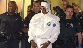 Markeith Loyd is escorted out of the Orlando Police headquarters in Orlando, Fla., Tuesday, Jan. 17, 2017. The suspect in the fatal shooting of an Orlando police officer was captured Tuesday night after eluding a massive manhunt for more than a week, authorities said. (Red Huber/Orlando Sentinel via AP)