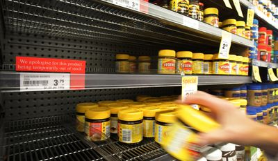 FILE- In this March 20, 2012, file photo, a customer takes a jar of Vegemite from next to an empty shelve in a supermarket in Auckland, New Zealand. Vegemite and other grocery products are being sold by Oreo-maker Mondelez to Australian dairy company Bega Cheese in a deal worth about $345.3 million (460 Australian dollars), Mondelez International Inc. said Wednesday, Jan. 18, 2017. (Sarah Ivey/New Zealand Herald via AP, File)