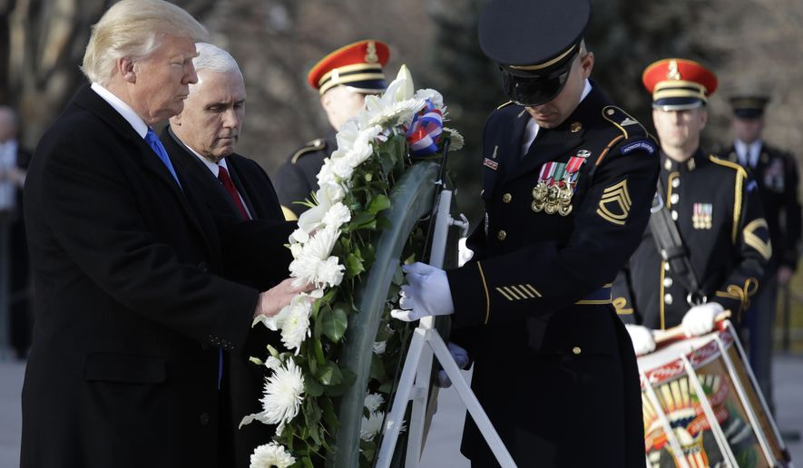 President-elect Donald Trump, accompanied by Vice President-elect Mike Pence places a wreath at the Tomb of the Unknowns, Thursday, Jan. 19, 2017, at Arlington National Cemetery in Arlington, Va., ahead of Friday's presidential inauguration. (AP Photo/Evan Vucci)