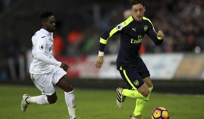 Arsenal's Mesut Ozil, right, Swansea City's Nathan Dyer battle for the ball during the English Premier League soccer match between Swansea City and Arsenal at the Liberty Stadium, Swansea, Wales, Saturday, Jan. 14, 2017.(Nick Potts/PA via AP)