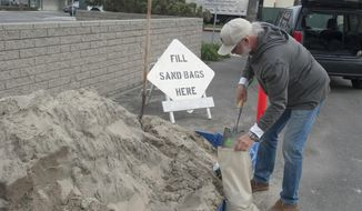 William Wright fills a few sandbags in the parking lot next to Fire Station 44 on 8th Street in Seal Beach, Calif., Wednesday, Jan. 18, 2017. The City of Seal Beach placed sand bags and piles of sand in several places around the city for residents to prepare for the coming winter storms. (Sam Gangwer/The Orange County Register via AP)