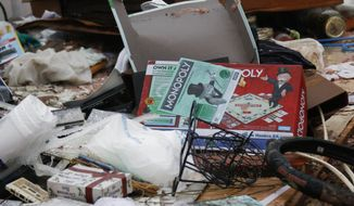 A boxed board game sits atop the remains of the possessions of Jessie and Diana Mills of the Pine Grove Community near Magee, Miss., following a direct hit by a possible morning tornado, Thursday, Jan. 19, 2017. Several homes and businesses were affected by the strong winds that blew through several central Mississippi counties. (AP Photo/Rogelio V. Solis)