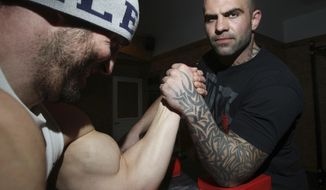 ADVANCE FOR USE SATURDAY, JAN. 21, 2017 AND THEREAFTER - In this Jan. 5,  2017 photo, Nick Brown, right, trains with Ben Booker owner of Second Chance Gym in Aurthur, Ill. Brown who has been a professional arm wrestler for 15 years is currently preparing to compete in a World Arm Wrestling League World Qualifier competition that will take place at the Penn Station event hall in Arthur on Saturday, February 25, 2017. (Jim Bowling/Herald & Review via AP)