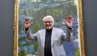 "SAP founder Hasso Plattner stands in front of the painting ""Water lily"" by Claude Monet in the newly opened Barberini Museum in Potsdam, eastern Germany, Thursday, Jan. 19, 2017. (Bernd Settnik/dpa via AP)"