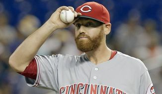FILE - In this July 8, 2016, file photo, Cincinnati Reds' Dan Straily adjusts his cap after a double by Miami Marlins' Christian Yelich in the first inning of a baseball game in Miami. A person familiar with the negotiations says the Marlins have acquired right-hander Dan Straily from the Cincinnati Reds for three minor leaguers. The person confirmed the trade to The Associated Press on condition of anonymity Thursday, Jan. 19, 2017, because it had not yet been announced. (AP Photo/Alan Diaz, File)