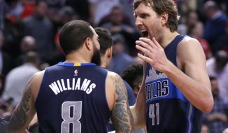 Dallas Mavericks' Dirk Nowitzki (41) and Deron Williams celebrate the Mavericks 99-98 win over the Chicago Bulls after an NBA basketball game, Tuesday, Jan. 17, 2017, in Chicago. (AP Photo/Charles Rex Arbogast)