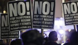 People attending an anti-Trump rally and protest hosted by filmmaker Michael Moore hold signs as they listen to speakers on a stage set up in front of the Trump International Hotel, Thursday, Jan. 19, 2017, in New York. President-elect Donald Trump, a New Yorker, is scheduled to take the oath of office Friday in Washington. (AP Photo/Kathy Willens)
