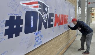 New England Patriots fan John Jones of Braintree, Mass., signs a banner at the Patriot Place shopping complex at Gillette Stadium in Foxborough, Mass., Friday, Jan. 20, 2017. The banner offers fans the opportunity to offer their words of encouragement to the team. The Patriots take on the Pittsburgh Steelers in the AFC championship game Sunday night. (Mark Stockwell/The Sun Chronicle via AP)