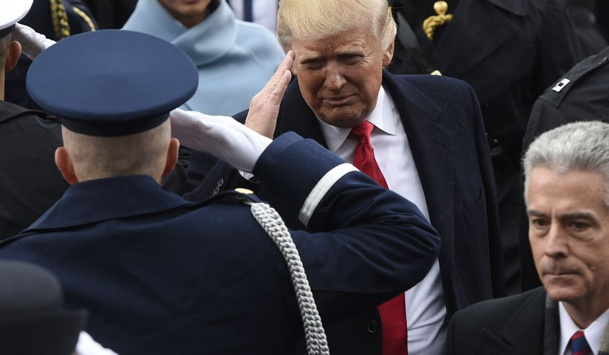 President Donald Trump salutes military personnel as he leaves Capitol Hill in Washington, Friday, Jan. 20, 2017, after taking the presidential oath.  (Saul Loeb/Pool Photo via AP) ** FILE **