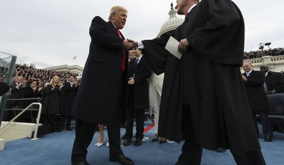 President Donald Trump shakes hands with Chief Justice John Roberts after taking the oath of office Friday, Jan. 27, 2017 on Capitol Hill in Washington. (Jim Bourg/Pool Photo via AP)