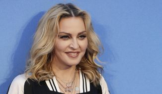 """FILE - In this Sept. 15, 2016 file photo, Madonna poses for photographers upon arrival at the World premiere of the film """"The Beatles, Eight Days a Week"""" in London. Madonna is trying to put a positive spin on President-elect Donald Trump's Friday, Jan. 20, 2017, inauguration. The superstar spoke at the Brooklyn Museum Thursday night, Jan. 19, with artist Marilyn Minter about art in a time of protest, among other things. (AP Photo/Kirsty Wigglesworth, File)"""