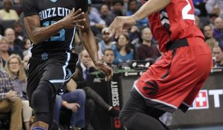 Charlotte Hornets' Kemba Walker, left, passes the ball around Toronto Raptors' Norman Powell during the first half of an NBA basketball game in Charlotte, N.C., Friday, Jan. 20, 2017. (AP Photo/Chuck Burton)