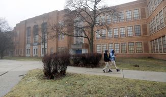"""Students walk outside Pershing High School, Friday, Jan. 20, 2017, in Detroit. Pershing is one of up to 38 schools in Detroit and other urban communities that the state hopes to close, potentially affecting 18,000 students and marking the first time that the state could close traditional public schools explicitly for academic reasons. Despite the announcement, some schools likely will remain open. State officials next will determine whether a closure would be an """"unreasonable hardship"""" for children with no better schools to attend (AP Photo/Carlos Osorio)"""