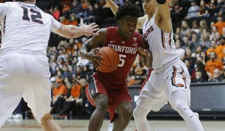 Stanford's Kodye Pugh, center, is guarded by Oregon State's Drew Eubanks, left, and JaQuori McLaughlin, right, during the first half of an NCAA college basketball game in Corvallis, Ore., Thursday, Jan. 19, 2017. (AP Photo/Timothy J. Gonzalez)