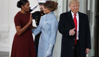 President-elect Donald Trump gives a thumbs-up as first lady Michelle Obama and Melania Trump talk at the White House in Washington, Friday, Jan. 20, 2017.  (AP Photo/Evan Vucci)