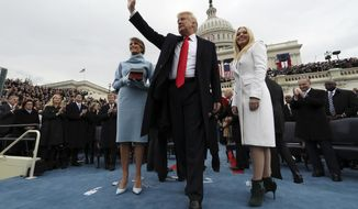 President Donald Trump waves after taking the oath of office as his wife Melania holds the Bible, and Tiffany Trump looks out to the crowd, Friday, Jan. 27, 2017 on Capitol Hill in Washington. (Jim Bourg/Pool Photo via AP)