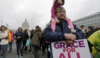 Michael Clark holds his daughter a rally before a women's march during the first full day of Donald Trump's presidency in San Francisco, Saturday, Jan. 21, 2017. (AP Photo/Jeff Chiu)