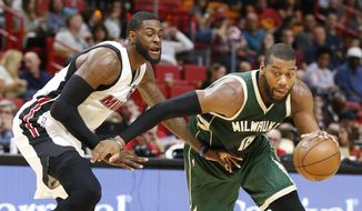 Milwaukee Bucks center Greg Monroe, right, drives past Miami Heat center Willie Reed during the first half of an NBA basketball game, Saturday, Jan. 21, 2017, in Miami. (AP Photo/Wilfredo Lee)