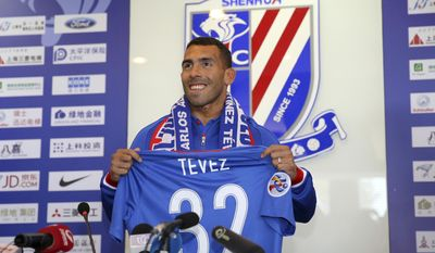 Argentine striker Carlos Tevez attends his first presser after joining Shanghai Shenhua in Shanghai, China Saturday, Jan. 21, 2017. Shanghai Shenhua has recruited Carlos Tevez reportedly with a deal that made the Argentine the highest-paid soccer player in the world. (Chinatopix Via AP)