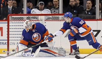 New York Islanders goalie Jean-Francois Berube (30) blocks a shot by the Los Angeles Kings as New York Islanders defenseman Adam Pelech (50) reaches for the rebound during the second period of an NHL hockey game, Saturday, Jan. 21, 2017, in New York. (AP Photo/Julie Jacobson)
