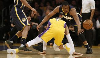 Indiana Pacers forward Thaddeus Young, right, takes the ball away as Los Angeles Lakers guard D'Angelo Russell, center, falls to the floor with an injury during the first half of an NBA basketball game in Los Angeles, Friday, Jan. 20, 2017. (AP Photo/Alex Gallardo)