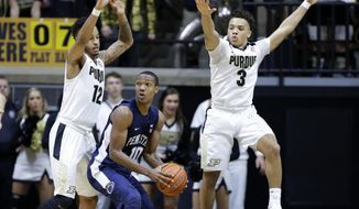 Penn State guard Tony Carr (10) is defended by Purdue forward Vince Edwards (12) and guard Carsen Edwards (3) in the second half of an NCAA college basketball game in West Lafayette, Ind., Saturday, Jan. 21, 2017. Purdue defeated Penn State 77-52. (AP Photo/Michael Conroy)