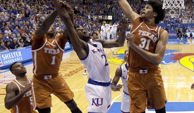 Kansas' Lagerald Vick (2) shoots under pressure from Texas' Andrew Jones (1) and Jarrett Allen (31) during the first half of an NCAA college basketball game Saturday, Jan. 21, 2017, in Lawrence, Kan. (AP Photo/Charlie Riedel)