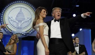 President Donald Trump acknowledges the crowd with first lady Melania Trump at the Freedom Ball, Friday, Jan. 20, 2017, in Washington. (AP Photo/Evan Vucci)