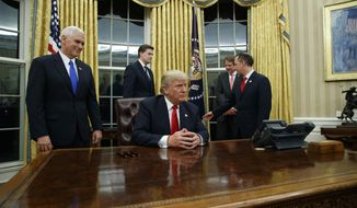 Vice President Mike Pence, left, watches as President Donald Trump prepares to sign his first executive order, Friday, Jan. 20, 2017, in the Oval Office of the White House in Washington. (AP Photo/Evan Vucci)
