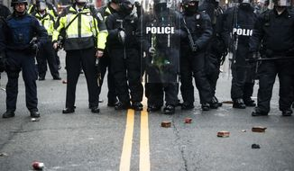 Bricks thrown by protestors rest at the feet of police officers during a demonstration after the inauguration of President Donald Trump, Friday, Jan. 20, 2017, in Washington. (AP Photo/John Minchillo)