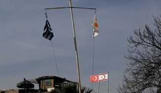 Greek and Cypriot flags fly next to a Turkish military guard post with Turkish and Turkish Cypriot breakaway flags between U.N. buffer zone. After decades of frustration, intensive talks between leaders of the Greek and Turkish Cypriot communities have created a sense of optimism to heal political divisions. (Associated Press)