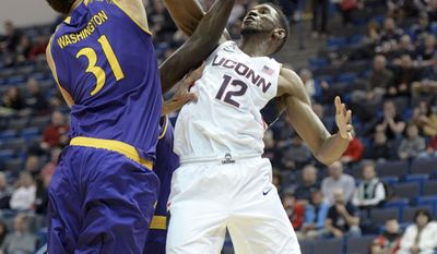 Connecticut's Kentan Facey (12) shoots over East Carolina's Andre Washington (31) during the first half of an NCAA college basketball game, Sunday, Jan. 22, 2017, in Hartford, Conn. (AP Photo/Stephen Dunn)