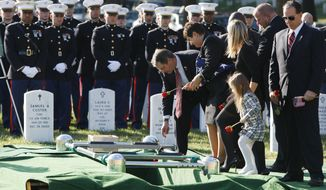 The family of Marine 1st Lt. Travis L. Manion drops roses into his gravesite during the reinternment ceremony for Manion, of Doylestown, Penn., at Arlington National Cemetery, in Arlington, Va. on Friday, Oct. 1, 2010. From center are Manion's father retired Marine Col. Thomas Manion, mother Janet Manion, sister Ryan Manion with her daughter Maggie Manion-Borek, 4, and brother-in-law David Borek. Manion was buried in Pennsylvania after being killed in Iraq in 2007, he is being reinterned at Arlington so that he can be buried next to his best friend, Marine Lt. Brendan Looney, who was killed in Afghanistan and will be buried on Monday. (AP Photo/Jacquelyn Martin)