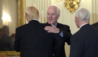 President Donald Trump, left, hugs Senate Majority Whip Sen. John Cornyn, R-Texas, center, as Vice President Mike Pence, right, watches, as they arrive for a reception for House and Senate leaders in the the State Dining Room of the White House in Washington, Monday, Jan. 23, 2017. (AP Photo/Susan Walsh)