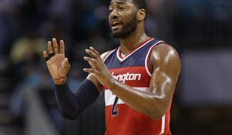 Washington Wizards' John Wall (2) directs the team against the Charlotte Hornets in the first half of an NBA basketball game in Charlotte, N.C., Monday, Jan. 23, 2017. (AP Photo/Chuck Burton)