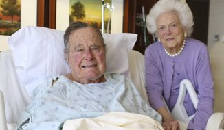 In this photo provided by Office of George H.W. Bush on Monday Jan. 23, 2017, former President George H.W. Bush and his wife Barbara pose for a photo at Houston Methodist Hospital in Houston. The 92-year-old former president is still suffering from pneumonia, but is well enough to leave the intensive care unit at a Houston hospital, doctors said Monday. His wife, Barbara, has been discharged from the same facility after completing treatment for bronchitis. (Courtesy the Office of George H.W. Bush via AP)