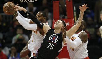 Los Angeles Clippers guard Austin Rivers (25) battles Atlanta Hawks center Dwight Howard (8) and forward Paul Millsap (4) for a rebound in the first half of an NBA basketball game, Monday, Jan. 23, 2017, in Atlanta. (AP Photo/John Bazemore)