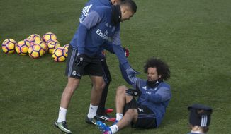 Real Madrid's Marcelo is helped up from the ground during a training session in Madrid, Spain, Friday Jan. 20, 2017. Real Madrid will play Malaga on Saturday in a Spanish La Liga soccer match after having lost their last two games. (AP Photo/Paul White)
