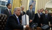 President Donald Trump shows off a signed executive order to reinstitute a policy barring any recipient of U.S. assistance from performing or promoting abortions abroad with money they receive from non-U.S. sources, Monday, Jan. 23, 2017, in the Oval Office of the White House in Washington. (AP Photo/Evan Vucci)