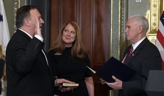 Vice President Mike Pence, right, swears in CIA Director Mike Pompeo, left, as Pompeo's wife Susan, center, watches in the Vice President's Ceremonial Office in the Eisenhower Executive Office Building in the White House complex in Washington, Monday, Jan. 23, 2017. (AP Photo/Susan Walsh)