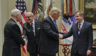 President Donald Trump, greets Matt Blunt, president of the American Automotive Policy Council, as Vice President Mike Pence greets Craig Glidden, Executive Vice President, Legal and Public Policy and General Counsel, before the start of a meeting with automobile leaders in the Roosevelt Room of the White House in Washington, Tuesday, Jan. 24, 2017. (AP Photo/Pablo Martinez Monsivais)