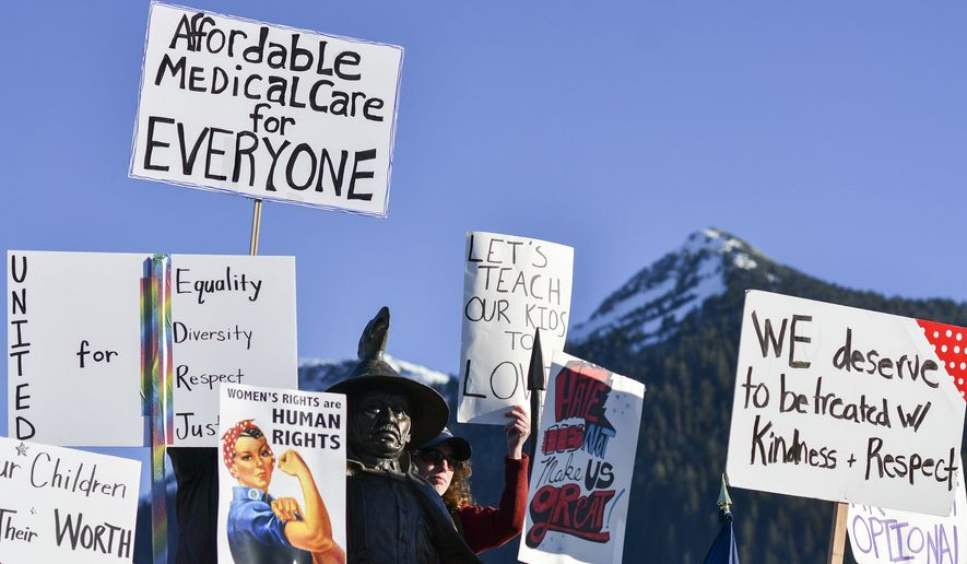 """People participating in the Women's March on Alaska stand in front of artist Dave Rubin's sculpture """"The Rock"""" on Saturday, Jan. 21, 2017, on Berth II in Ketchikan, Alaska. (AP Photo/Taylor Balkom)"""