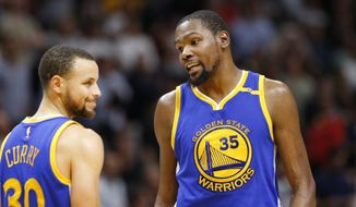 Golden State Warriors forward Kevin Durant (35) talks with guard Stephen Curry (30) during the second half of an NBA basketball game against the Miami Heat, Monday, Jan. 23, 2017, in Miami. The Heat defeated the Warriors 105-102. (AP Photo/Wilfredo Lee)
