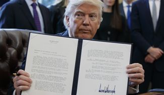 President Donald Trump shows off his signature on an executive order about the Dakota Access pipeline, Tuesday, Jan. 24, 2017, in the Oval Office of the White House in Washington. (AP Photo/Evan Vucci)