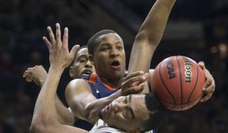 Virginia's Devon Hall, center, competes for a rebound with Notre Dame's Bonzie Colson, front, during the first half of an NCAA college basketball game Tuesday, Jan. 24, 2017, in South Bend, Ind. (AP Photo/Robert Franklin)