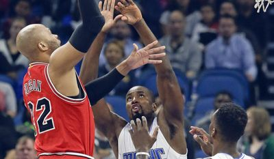 Chicago Bulls' Taj Gibson, left, takes a shot over Orlando Magic's Serge Ibaka, center, and Jeff Green (34) during the first half of an NBA basketball game, Tuesday, Jan. 24, 2017, in Orlando, Fla. (AP Photo/John Raoux)