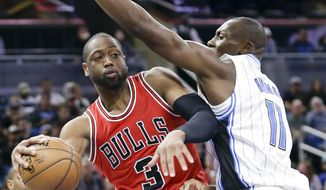 Chicago Bulls' Dwyane Wade, left, passes the ball around Orlando Magic's Bismack Biyombo (11) during the second half of an NBA basketball game, Tuesday, Jan. 24, 2017, in Orlando, Fla. Chicago won 100-92. (AP Photo/John Raoux)